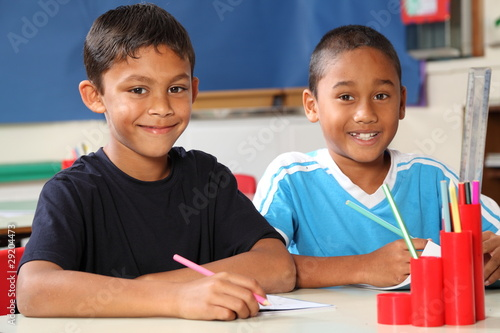 Two happy school boys sitting to their desk in class