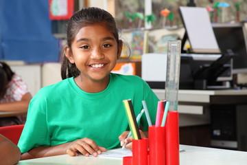 Schoolgirl brilliant smile at her desk in class