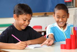 Two happy school boys sharing learning in class