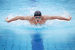 Swimmer in cap breathing performing the butterfly stroke - 29207612