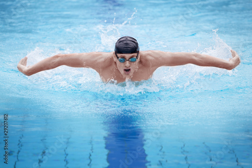 Poster, Tablou Swimmer in cap breathing performing the butterfly stroke