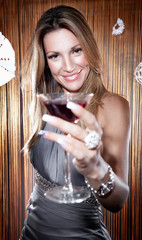 Beautiful young woman holding a glass of red wine