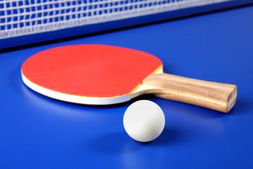 raqueta roja y una pelota de tenis de mesa