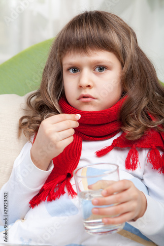 Little sick girl with scarf in bed is taking a pill