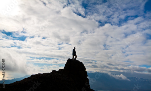 Silhouette of woman on the top of the rock