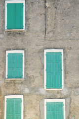 Closed green window shutters on a gray house facade