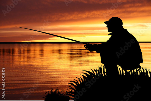 Fisherman sitting with fishing tackle at sunrise