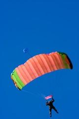 Parachuter descending with a red parachute against blue sky