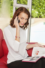 Young woman using iPhone, holding magazine