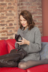 Young woman opening wallet