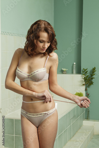 Young woman in underwear measuring waist