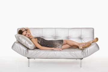 Young woman in formalwear sleeping on sofa