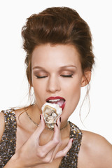 Young woman eating oyster