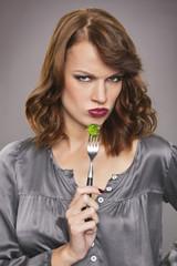 Young woman eating broccoli