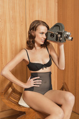 Young woman in underwear using old-fashioned movie camera