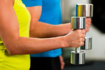 Paar mit Hanteln im Fitnessstudio