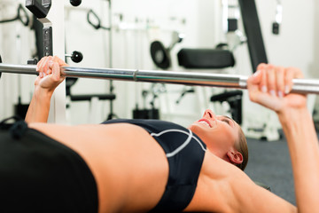 Frau im Fitnessstudio trainiert mit Langhantel