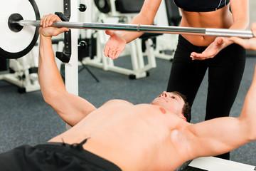Mann im Fitnessstudio trainiert mit Langhantel