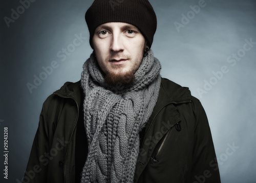 Artistic dark portrait of the young beautiful man in a cap and a