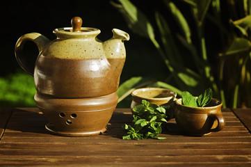 Teekanne mit Tassen und Pfefferminzblättern