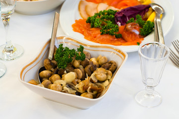 Plate with vinegar pickled mushrooms on table, small jigger