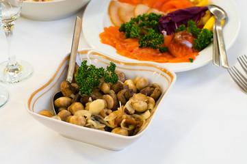 Plate with vinegar pickled mushrooms on dinner table