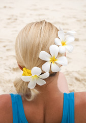 Woman sitting on the beach with flowers in her hair