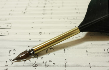 Vintage quill on classical music sheets