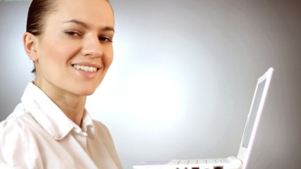 Smiling young woman with laptop, grey background