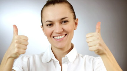 Woman gesturing a thumbs up sign, grey background