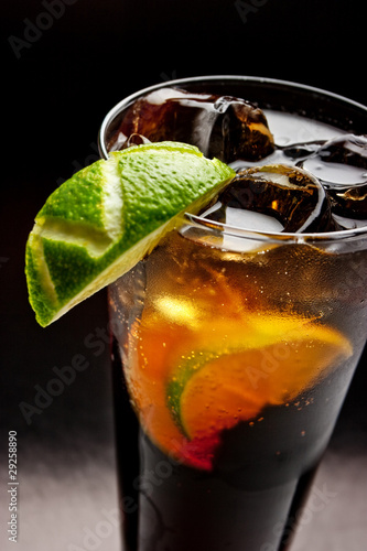 cold tea with lime and ice (close up) on dark background