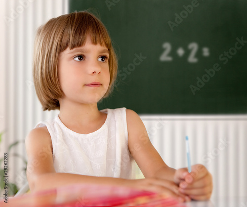 Elementary school pupil writing in a classroom