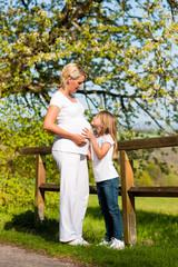 Schwangerschaft - Mädchen berührt schwangere Mutter