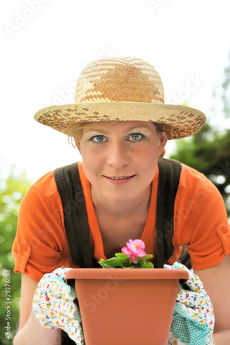 Young woman - gardening - potting Begonia