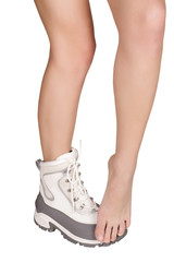 slender nude legs in the winter tourist boots on a white backgro