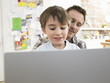 Boy 3-6 using laptop with father at home