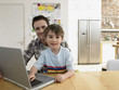 Boy 3-6 using laptop with father in kitchen, portrait