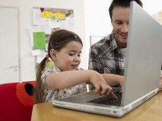 Girl 3-6 using laptop with father at home