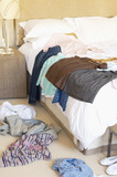Clothes scattered on Floor and Bed of hotel room