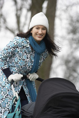 Mother walking with baby carriage in park, portrait