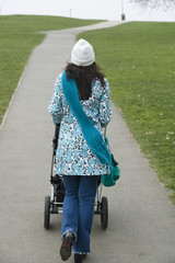 Back view of mother pushing stroller in park
