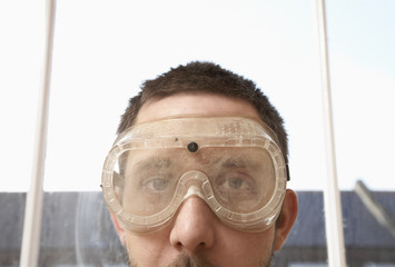 Man wearing protective eye goggles near window, close up, high section