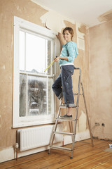 Woman  standing on step ladder in unrenovated room