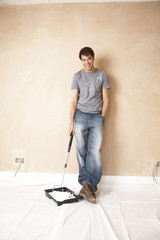 Man holding paint roller in paint tray, in unrenovated room, portrait
