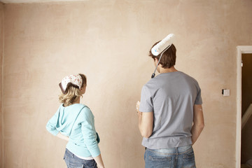 Couple looking at wall of unrenovated room, back view