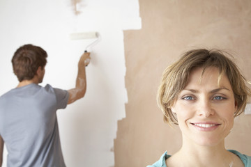 Woman smiling while man roller paints interior wall