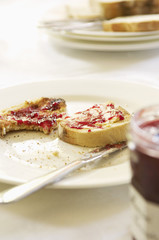 Half-eaten toast with jam on plate with butter knife, close-up