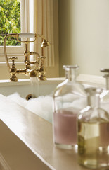 Bottles of Bath Oils on edge of bathtub filled with bubbles, water running from tap