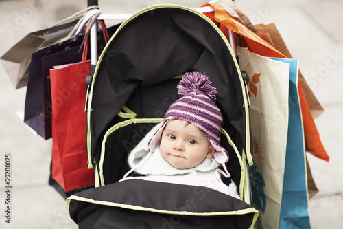 Baby sitting in stroller hung with shopping bags, outdoors