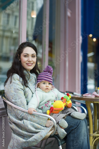 Mother with baby on her laps sitting outside cafe